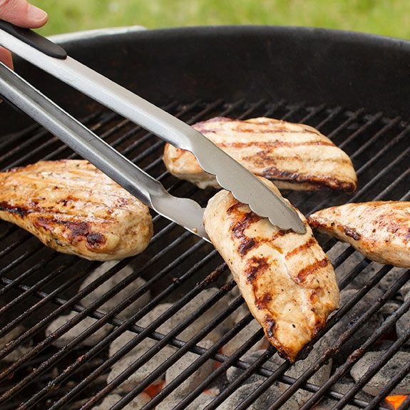 Four chicken breasts with grill marks on them sitting on a circular grill. Metal tongs are being used to pick up the one closest to the camera