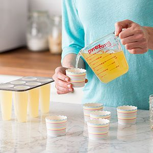 Person pouring a yellow liquid from a measuring cup into a striped cup. A filled plastic mold sits to the side and empty cups little the countertop in front of the person