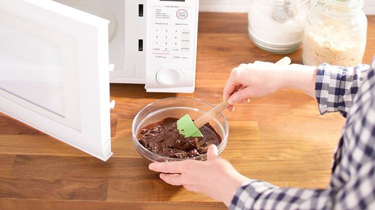 Person using a green spatula to stir melting chocolate in a bowl straight from their now open microwave