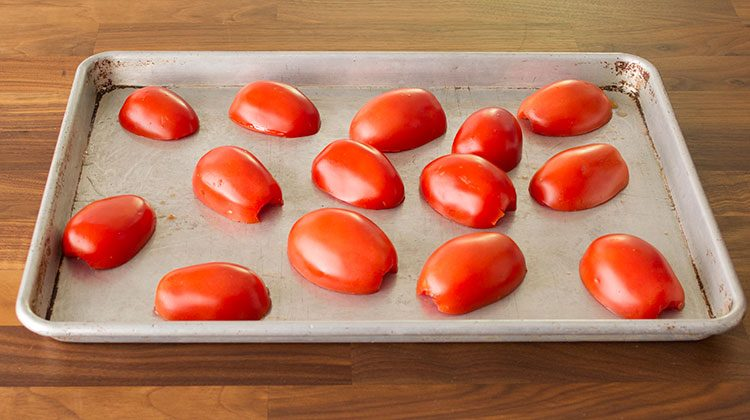 Halved tomatoes scattered on a baking sheet