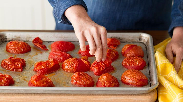 Halved and wrinkled tomatoes on a baking sheet that a person is reaching into to remove their peels