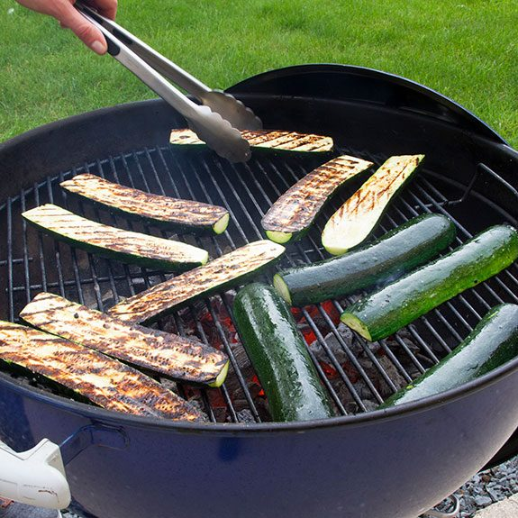 Zucchini sliced length-wise and cooking on a charcoal grill as a person with metal tongs flips them