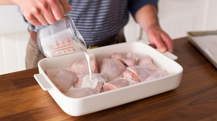 Raw chicken parts in a flat dish with high sides having buttermilk poured over them from a measuring cup
