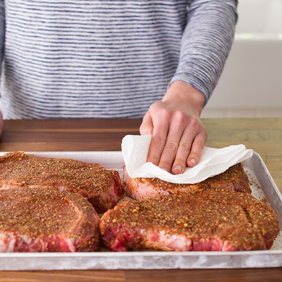 Raw, seasoned steaks being patted with a paper towel