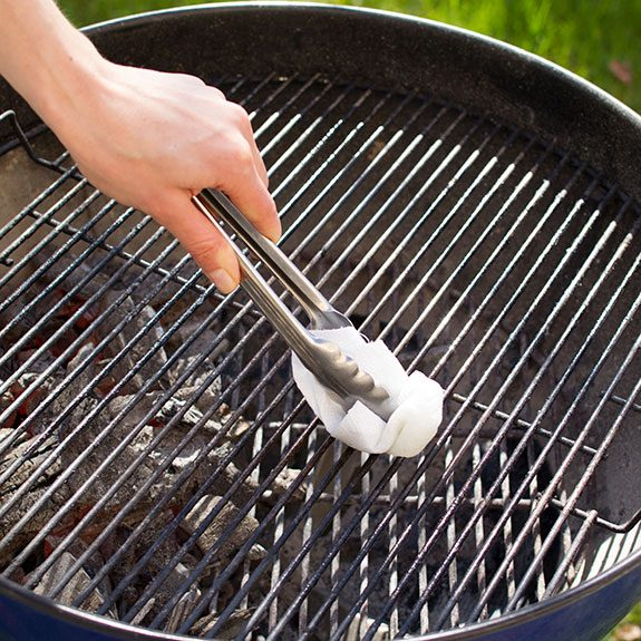 Person using paper towel held in metal tongs to grease their circular grill