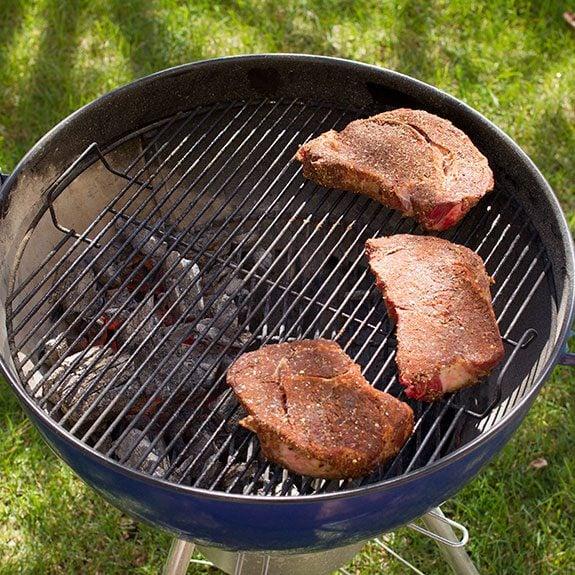 Three seasoned steaks on a circular grill
