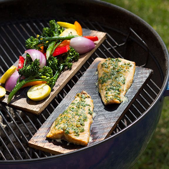 Two planks on the grill, one with a fish fillet and the other covered in various chopped veggies