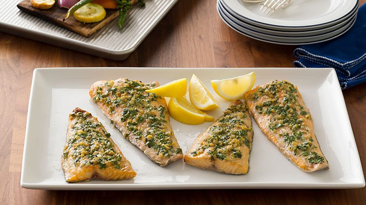 Four perfectly grilled and seasoned fish fillets on a long white, rectangular plate with lemon wedges