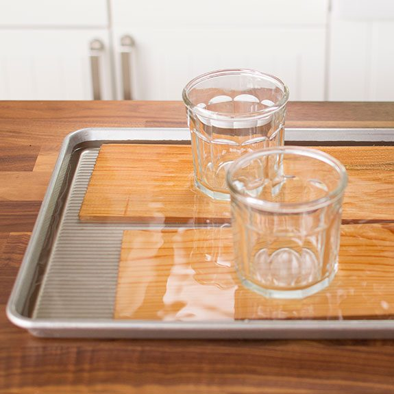 Two planks of wood submersed in water on a baking sheet with glass cups holding them under