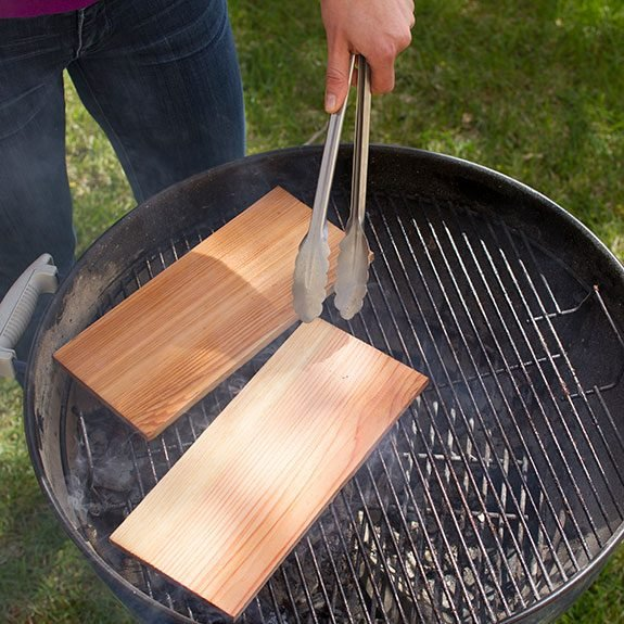 Pre-soaked plank on the grill being moved into place with metal tongs