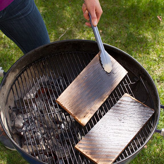 Person using metal tongs to hold up one of the planks as they start to blacken