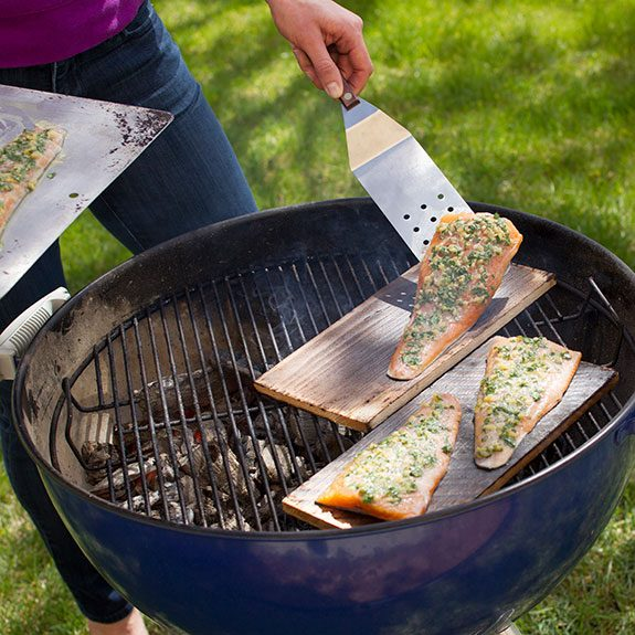 Person using a metal spatula to place their fillets on the planks skin-side down