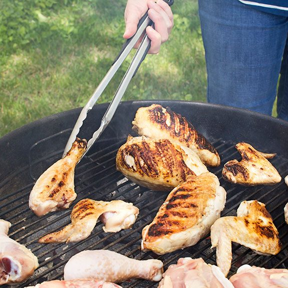 Person using metal tongs to flip chicken parts as they cook on the grill and brown