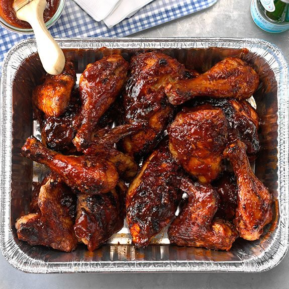 Aluminium pan filled with bbq chicken wings, legs, and thighs with a beer and blue plaid napkin waiting to the right