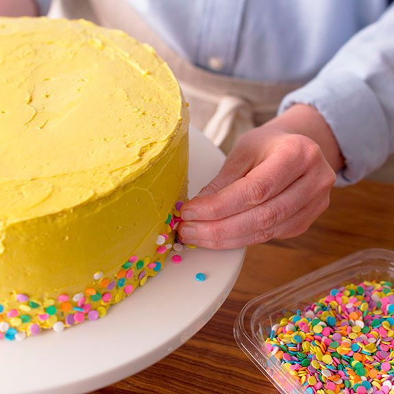 Colorful sprinkles are being stuck onto the yellow buttercream frosting of a cake