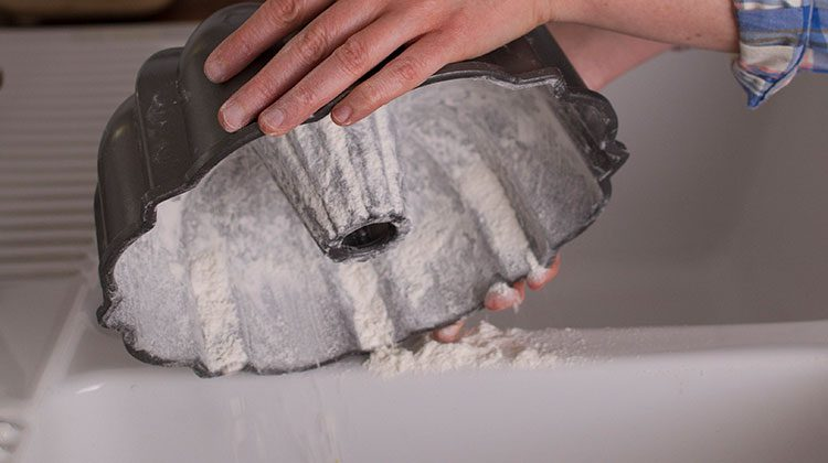 A bundt cake pan with its inside coated in flour is being held upside down over a sink