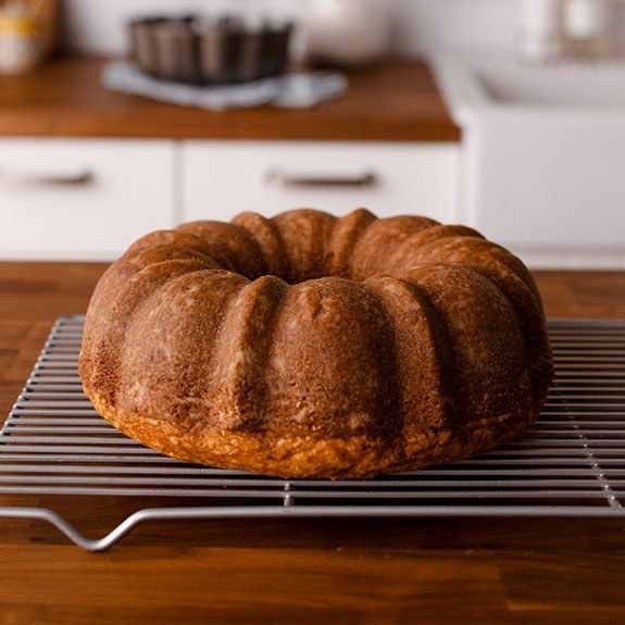 Baked, golden brown bundt cake sitting on a wire rack to cool