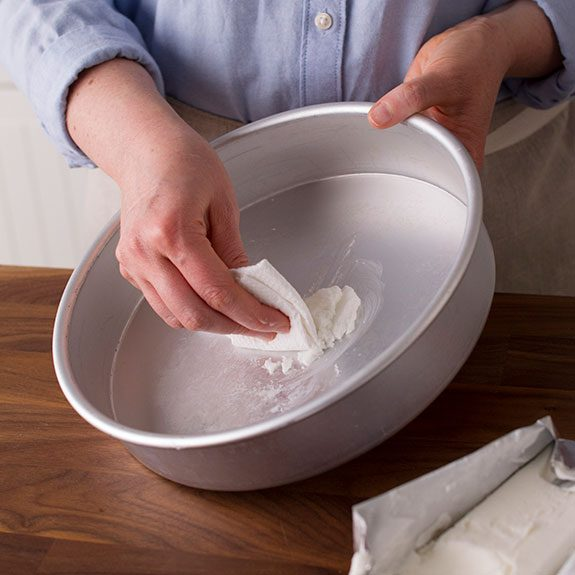 hand greasing a cake pan with a generous dollop of grease on a square of parchment paper