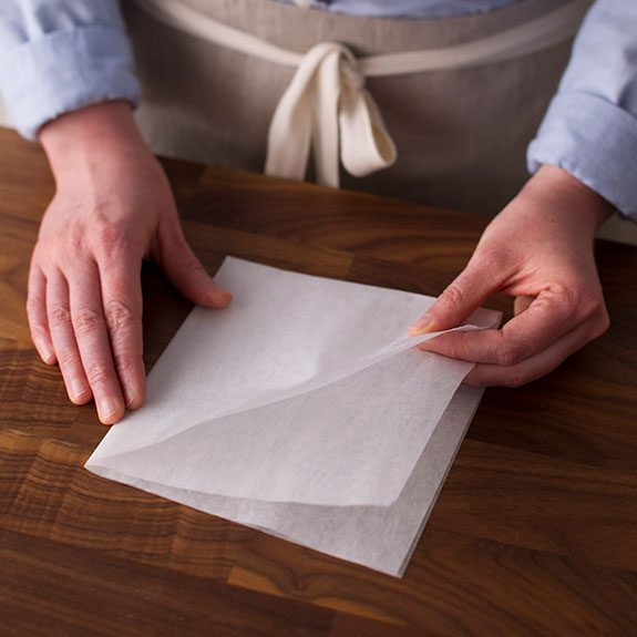 Person with a square of parchment paper in front of them