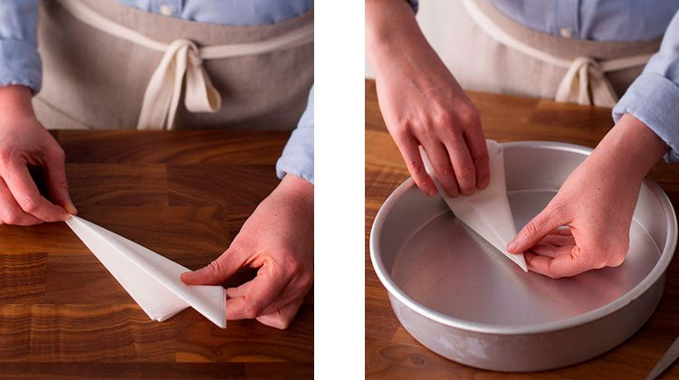Person folding parchment paper into triangles then lining it up within a cake pan