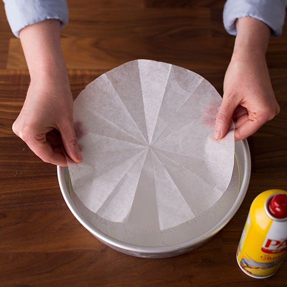 person holding a circular liner over a cake pan