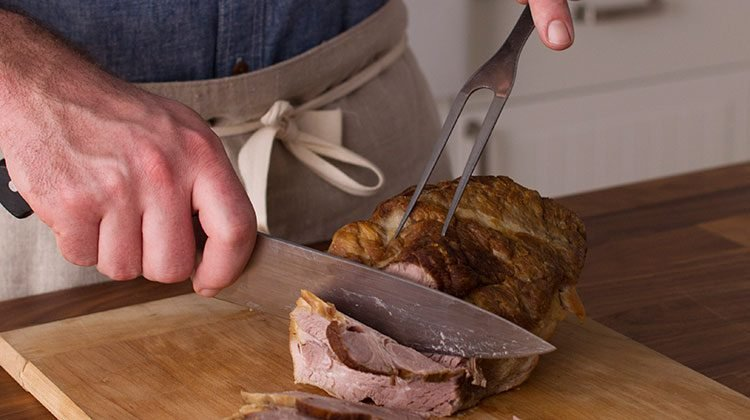 man using a carving knife to carefully cut cooked pork shoulder into slices