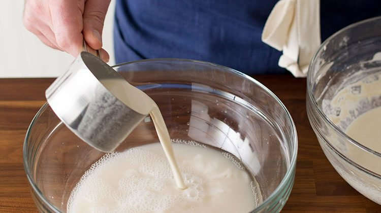 person pouring sourdough starter from a measuring cup into the mixture
