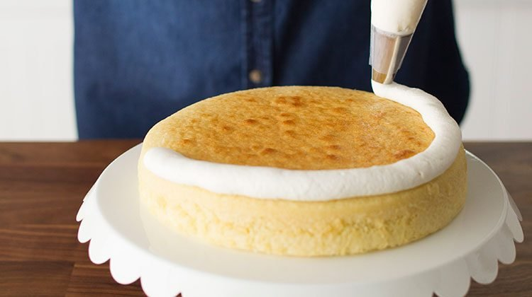 Piping a single layer of white frosting onto a layer of cake on a serving plate