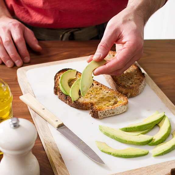 Person arranging four slices of avocado on top of a piece of toast