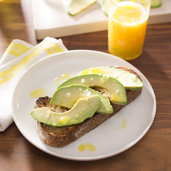 Toast with slices of avocado and topped with salt and olive oil