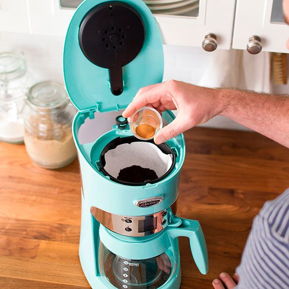 Person pouring spice into the top compartment of a bright blue coffee maker