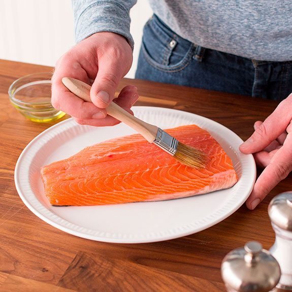 Person slathering a salmon with olive oil using a brush