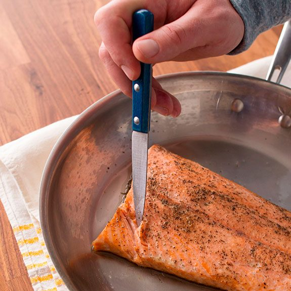 Filet of salmon cooking in a skillet as a person inserts a knife to check if the filet flakes