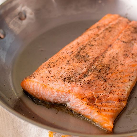 Filet of salmon cooking in a skillet
