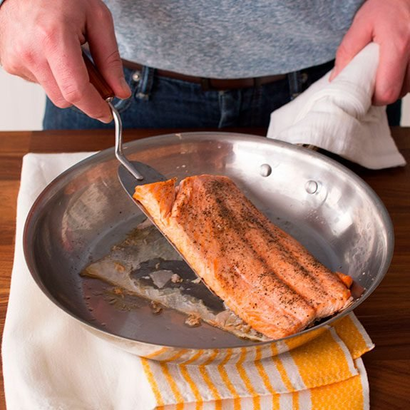 Person using a metal spatula to remove their salmon from the skillet, the skin of the fish being left behind as it sticks to the surface