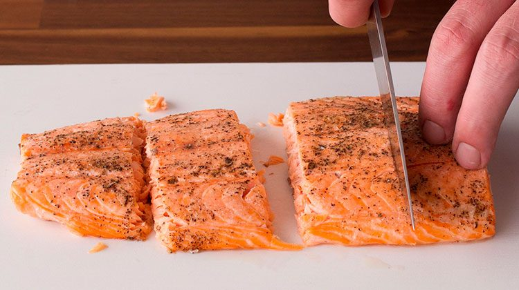Person slicing a cooked salmon filet into four pieces on a white cutting board