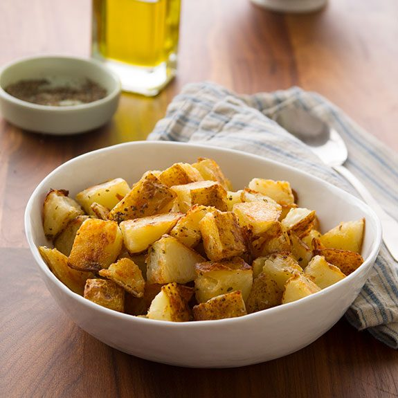 Bowl of roasted, cubed potatoes beside a towel and spoon