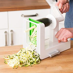 Zucchini being pressed through a spiralizer with half of it already out the other end in neat curls