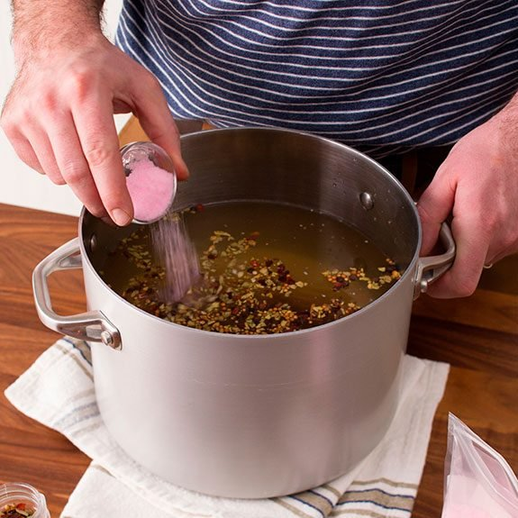 large metal pot filled with water and seasonings