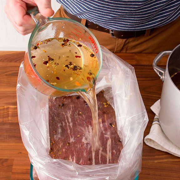 beef in an oven bag with brine being poured onto it from a measuring cup