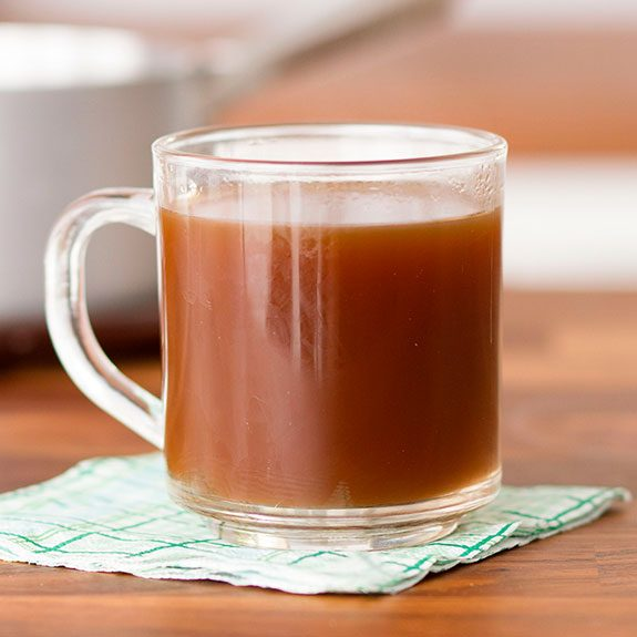 Cup filled with bone broth sitting on a green plaid napkin