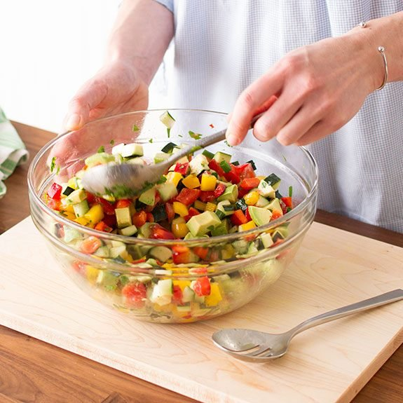 Person stirring the vinaigrette together with the chopped vegetables with a spoon