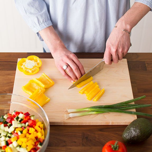 Person slicing a yellow pepper on a wooden cutting board