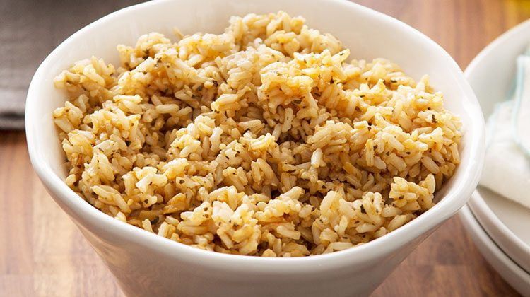 cooked brown rice fills an oblong white bowl
