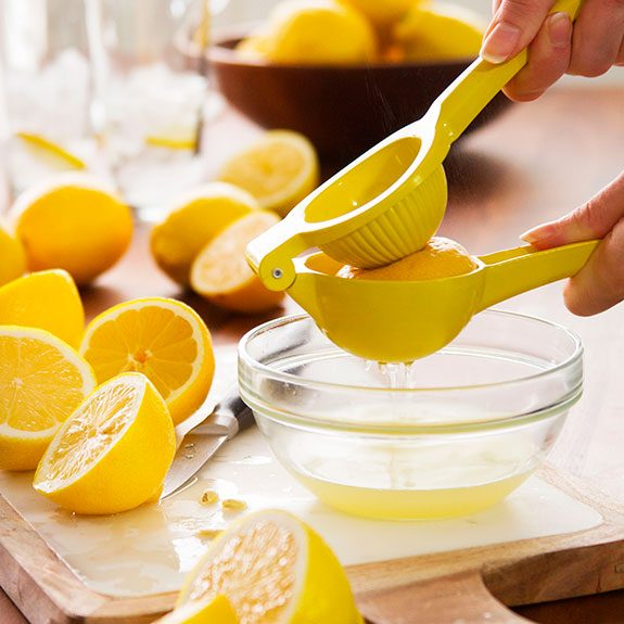 person using a squeezer to empty the juice from a lemon and into a bowl