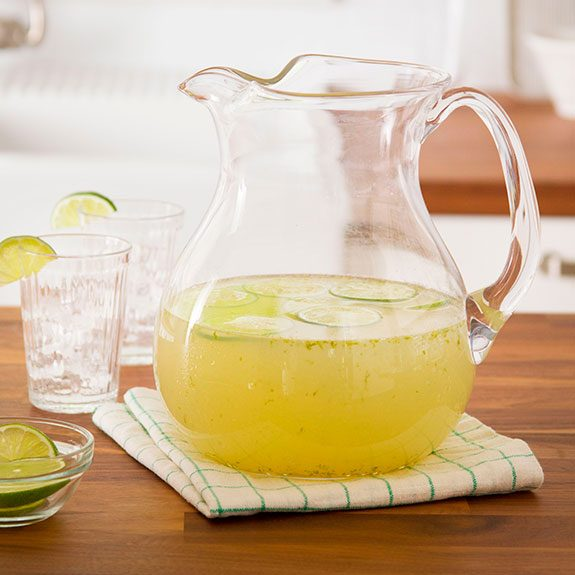 large glass pitcher half full of lemonade with slices of lime floating on top
