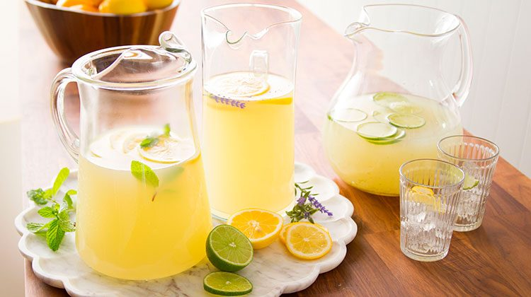 three full pitchers of lemonade sitting together surrounded by filled glasses