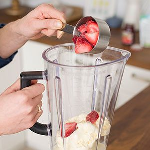 Person pouring strawberries from a metal measuring cup into a blender