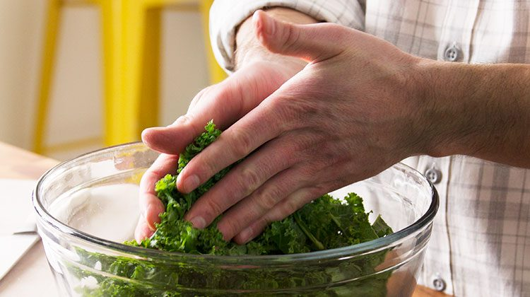 person massaging kale that is within a glass bowl