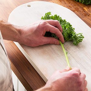 Person pulling kale leaves carefully from the stem with their hands